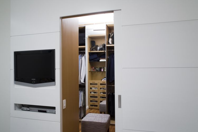 O Studio Costa Marques projetou este closet. Ele  separado do quarto por um painel (que abriga a TV) e acessado por uma porta de correr, ambos de madeira freij linheiro com acabamento de laca branca
