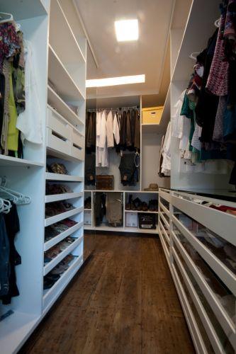 Closet projetado pelo Studio Costa Marques. Os armários não têm portas e são repletos de prateleiras e gavetas, além dos varões para cabides