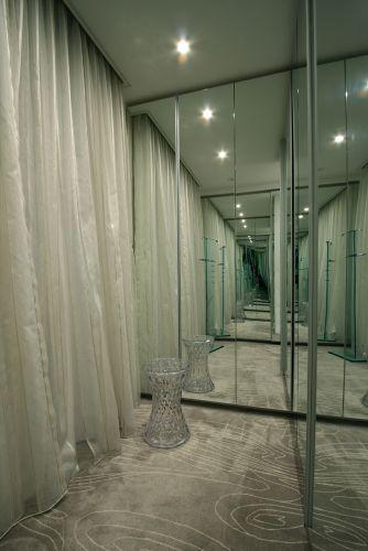 Closet projetado por Sueli Adorni. A arquiteta e decoradora escolheu o carpete Avanti para revestir todo o espaço. Os armários são da Segatto e a iluminação foi realizada pela Puntoluce. Nesse ângulo, aparecem os espelhos da Glass Company e a cortina com tecido da Celina Dias