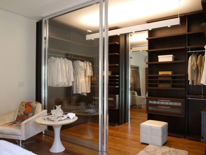 Dividido por uma porta de correr de vidro transparente, o closet foi projetado pela arquiteta Denise Barretto. O piso de madeira foi o mesmo utilizado no dormitório. Os armários, sem portas, têm muitas prateleiras