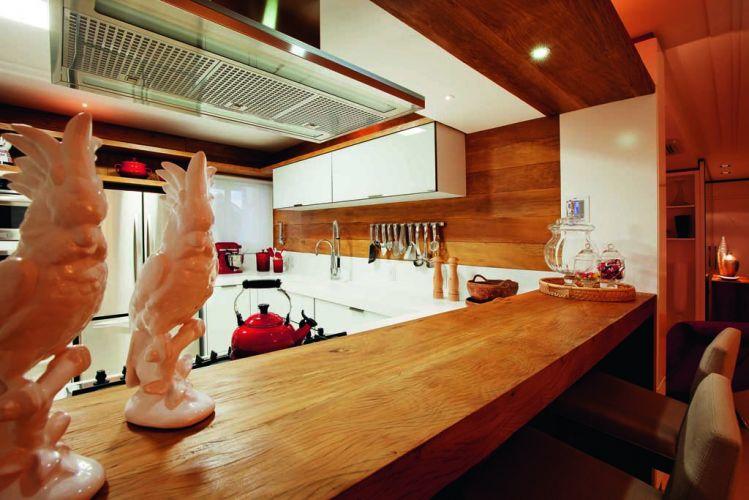 Antes tradicionalmente fechada e localizada ao fundo do apartamento, a cozinha mudou de lugar: tomou um pedaço da sala e da varanda e tornou-se parte integrante da área social. É ali que o