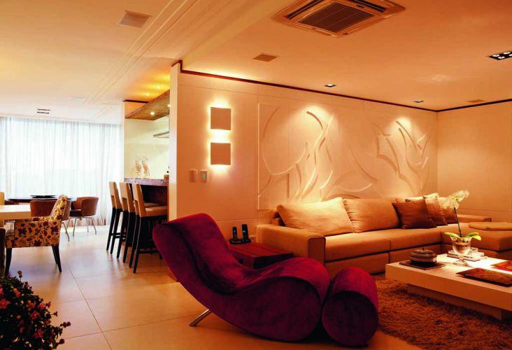 Nas paredes do home theater, arandelas quadradas emitem luz indireta e dão ao ambiente um efeito de cinema. Em primeiro plano, a chaise vermelha