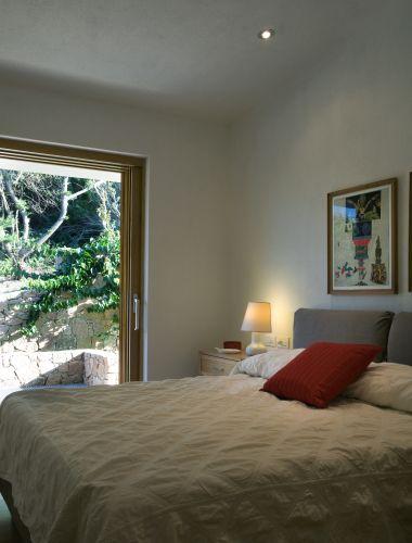 Em um dos quartos da casa na Sardenha (Itália), de Cossu & Tedesco Arquitetos, a cama com cabeceira estofada em sarja é da Ikea