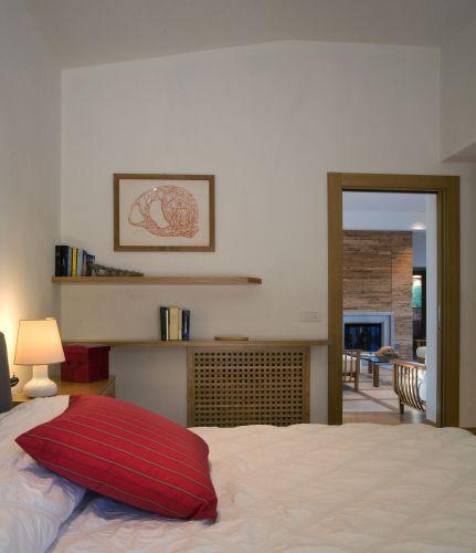 Em um dos quartos da casa na Sardenha (Itália), de Cossu & Tedesco Arquitetos, o teto acompanha o desenho do telhado, trazendo mais aconchego à suíte. Carvalho, nas portas e na marcenaria executada pela Savigni