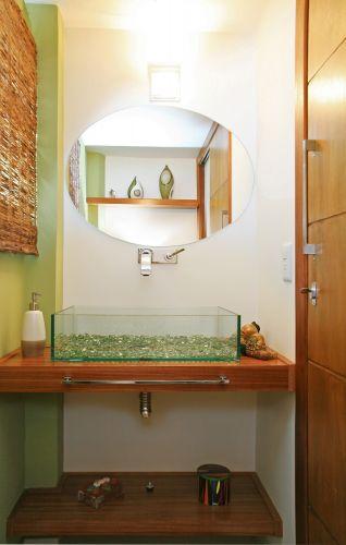 Atração do lavabo, a cuba de vidro feita sob medida e forrada de bolinhas de gude dá um toque lúdico ao ambiente. A bancada de madeira incorpora o toalheiro, racionalizando o espaço. Repare no reflexo do espelho e o nicho criado sobre o vaso, com objetos decorativos