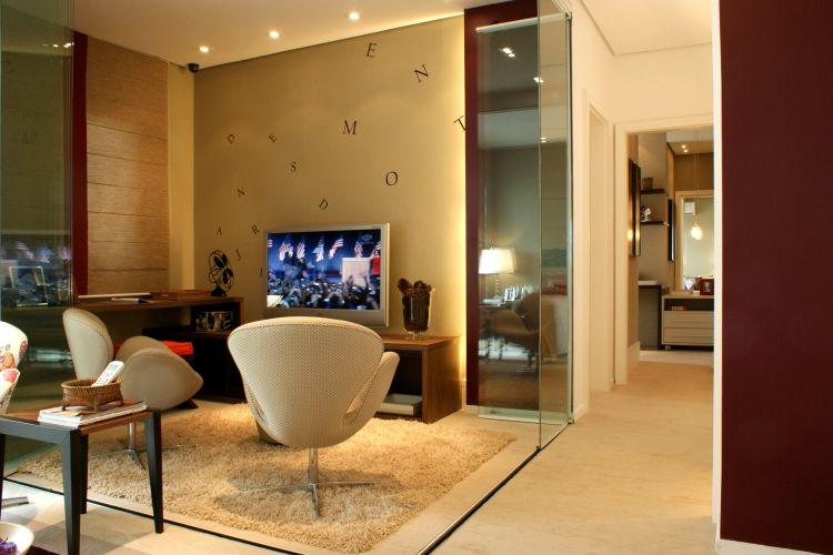 A sala de TV tem poltronas giratórias Swan (design de Arne Jacobsen) e pode ser isolada dos outros ambientes pelos painéis de vidro. Móvel e bancada da Florense abrigam a TV e a área de trabalho. Para quebrar a neutralidade, a parede recebeu adesivos com letras de vários tamanhos. A luz focada, embutida no forro, clareia os equipamentos
