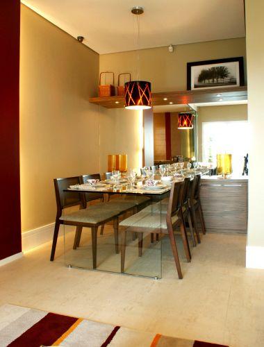 Na sala de jantar, dois truques que ajudam a driblar a falta de espaço: o espelho na parede do fundo, que aumenta a sala e multiplica a luz, e a marcenaria, que criou armário e prateleiras discretos. O pendente da Trust traz um toque de cor. Os móveis são da Grado