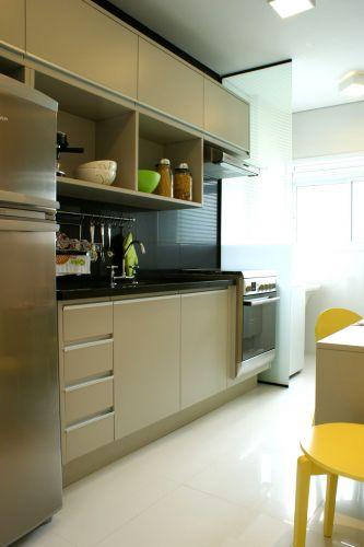 A cozinha planejada Florense, disposta em linha, embute fogão, pia e abriga a geladeira. Um painel de vidro fosco separa-a do serviço