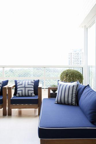 No terraço, móveis de linhas retas e madeira natural da Casual Exteriores com estofamento da Again, na única cor que o arquiteto elegeu para compor com os tons claros dominantes dos ambientes, o azul