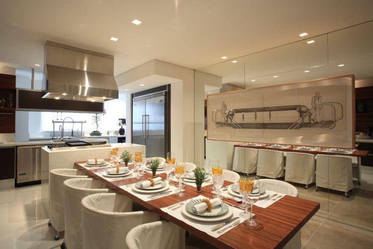 Na proposta do arquiteto David Bastos, a mesa em cedrinho é acompanhada pelas cadeiras da Casual Indoor Flexform que receberam capas de sarja. Para abrigar a geladeira, foi feito um nicho de gesso. Na parede espelhada, carvão sobre papel do baiano Vauluizo Bezerra.