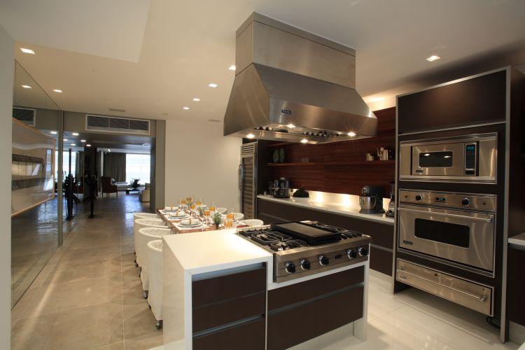 Na proposta do arquiteto David Bastos, a ilha da cozinha ocupa posição de destaque, junto ao jantar, e foi revestida de mármore perfect white da MG Mármores