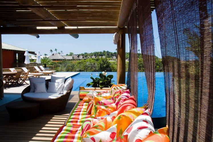 Vista do deck de cumaru a partir da varanda com cobertura de pergolado, elementos que contornam a generosa piscina