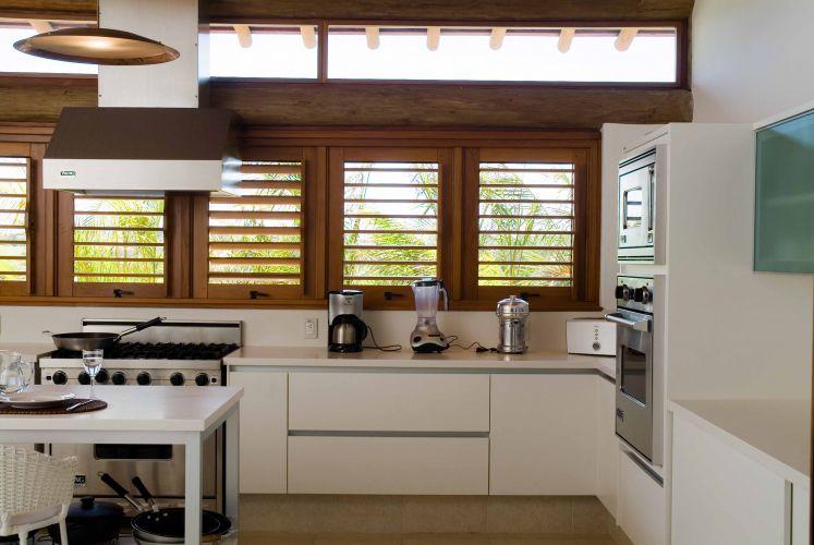 Apesar do mobiliário branco e dos eletrodomésticos de inox, a cozinha tem aspecto despojado conferido pelas venezianas de madeira
