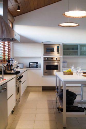 Apesar do mobiliário branco e dos eletrodomésticos de inox, a cozinha tem aspecto despojado conferido pelas venezianas de madeira. Destaque para o forro de madeira que acompanha a inclinação do telhado.