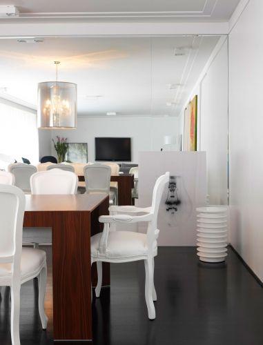 Além do lustre, a sala de jantar tem outros pontos de destaque como as cadeiras Luís XV emborrachadas. Junto ao espelho, uma fotografia de Valentino Fialdini impressa em metacrilato