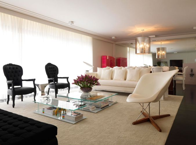 Assim como as paredes de um branco puríssimo contrastam com o assoalho ebanizado, o moderno e o clássico se alinham na composição do living. Cadeiras Luís XV dividem espaço com a La Chaise, de Charles e Ray Eames (à dir.)