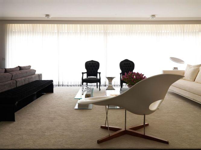 Luz natural em abundância ilumina o living que se divide em peças escuras, como as cadeiras Luís XV, e claras como La Chaise