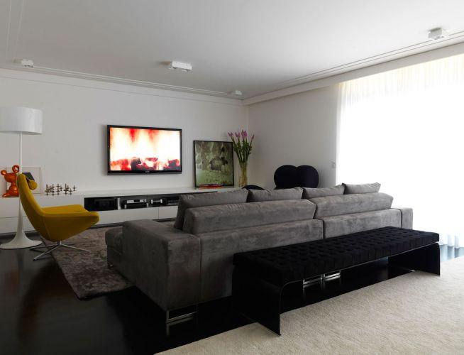 Sofás e poltronas confortáveis compõem o home do apartamento. Os destaques do espaço são as poltronas Metropolitan (em amarelo) e Donna (em azul marinho)