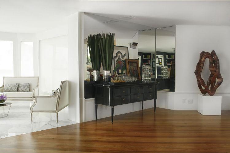 À esquerda, lounge que foi projetado no espaço que, originalmente, era a varanda do apartamento. Na área social, onde o piso é de madeira, foi colocada uma antiga cômoda que, após laqueada, faz as vezes de um bar. À direita, há uma obra de arte criada pela artista plástica que reside neste apartamento, em São Paulo
