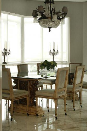 O piso de mármore já revestia a sala de jantar, antes da reforma do apartamento. O arquiteto Diego Revollo recuperou o revestimento e construiu um aparador, também de mármore, diante das janelas (onde estão apoiados os castiçais). A mesa antiga, do acervo dos proprietários, passou por uma restauração, assim como as cadeiras Jansen. Iluminando a mesa, lustre modelo império, com cristais Baccarat. Foi reformado e recebeu pequenas cúpulas, deixando o acessório mais moderno