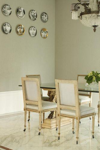 Em volta da antiga mesa, cadeiras Jansen, autênticas. Com rodinhas nos pés, as peças tiveram a pintura (pátina) refeita e os revestimentos dos estofados trocados. O tecido escolhido foi o linho, combinando com o papel de parede, que parece feito com o tecido. Uma coleção de pratos Fornasetti decora o ambiente