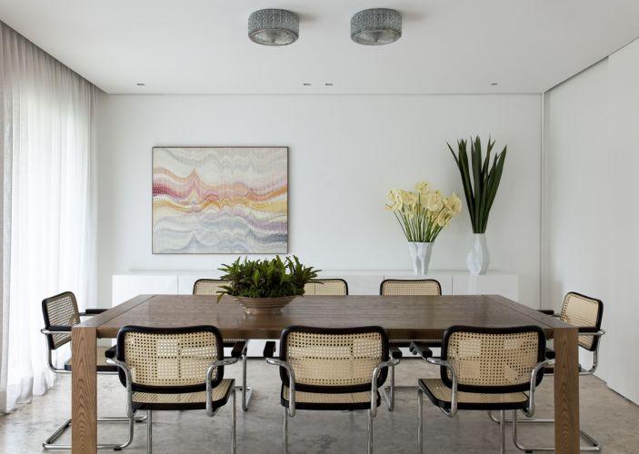 A ambientação da sala de jantar apresenta uma atmosfera de requinte e leveza. A mesa Rex, da Grado, de carvalho americano com tampo e pés chanfrados, é rodeada pelas cadeiras Cesca, de madeira ebanizada, assento e encosto de palha e pés de aço inox polido, da Tempos Modernos. A tela de Abraham Palatnik, da Galeria Nara Roesler, foi descentralizada permitindo a colocação de objetos decorativos, como os vasos da Érea apoiados no bufê de laminado branco com portas facetadas