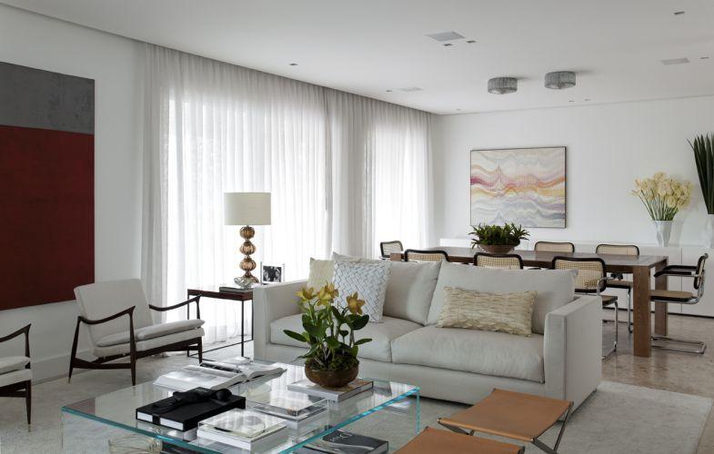 Vista geral da integração das salas de estar e jantar, com acesso ao terraço. O teto rebaixado em gesso embute spots no frame Hidden, da Wall Lamps. A mesa de jantar recebe a iluminação dos plafons de cristal da Dominici