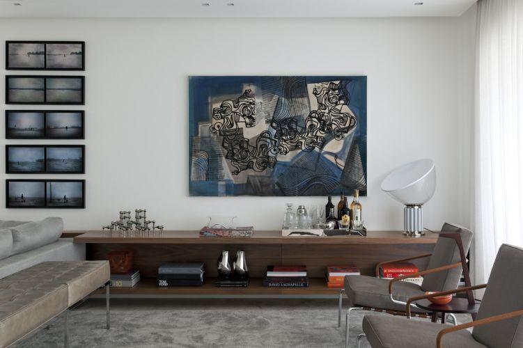 O lounge ganhou uma atmosfera acolhedora com a instalação de uma estante baixa executada pela Marcenaria Inovart. O móvel, elevado 12 cm do piso, se prolonga por toda a extensão da sala e é encimado pela tela do arquiteto-paisagista Burle Marx e por uma sequência de cinco fotografias. A luminária da On-Light distribui luz por todo o ambiente. Duas poltronas com braços revestidos de couro e estofados de linho, da Atrium, incrementam o aconchego
