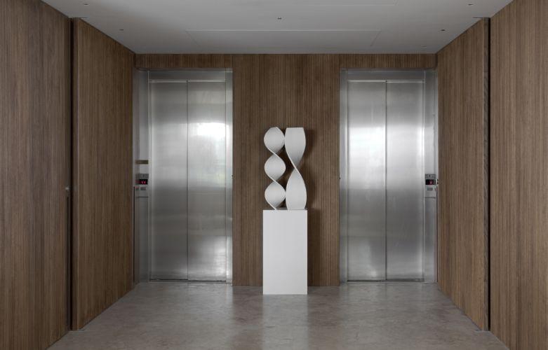 O hall de entrada foi integrado ao living e ganhou portas e painéis de nogueira americana contrastando com as portas de aço dos elevadores e com o piso revestido com mármore travertino levigado. O toque de arte é dado pela escultura Múltiplo 34, do artista Ascânio MMM, da Dan Galeria
