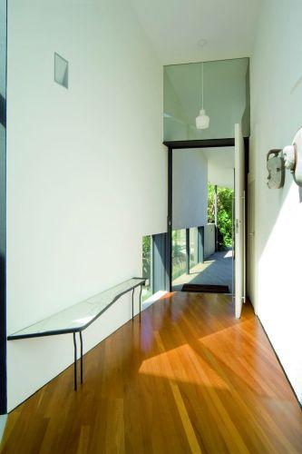 Entrada principal no segundo pavimento da casa Holman, em Sydney, na Australia, com paredes brancas e piso de assoalho de madeira. As guarnições e os batentes das portas são na cor preta