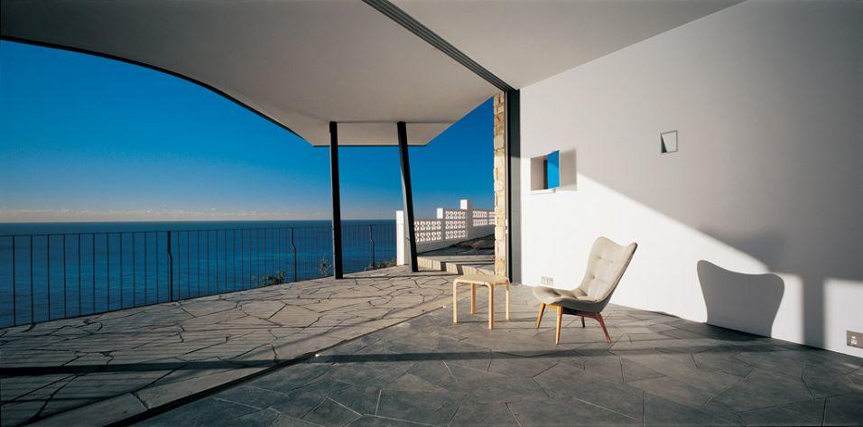 Terraço coberto sob a área social com piso de cacos de pedra e vista para o mar, na casa Holman, de Durbach Block Jaggers Architects, em Sydney, Australia