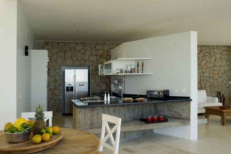 A cozinha da casa construída por Enrico Benedetti no litoral de São Paulo é separada do ambiente de estar por uma parede revestida com pastilhas que, entretanto, não atinge o teto. O recurso confere leveza ao ambiente, que se integra ao terraço e à área de refeições por meio do balcão construído com concreto, e com tampo de pedra negra