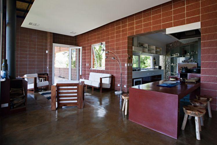 Living integrado à cozinha através da mesa em concreto, com acabamento em cimento queimado vermelho, ligada ao fogão caipira. Parede em tom avermelhado de bloco de concreto Stone, piso de cimento queimado natural e forro de madeira pintado suspenso