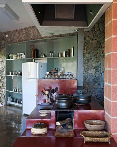 A parede ao fundo da cozinha foi revestida de pedra rachão dando um ar mais rústico. O nicho foi ocupado por uma estante simples de madeira pintada em tom mais frio, em contraste com o pigmento vermelho do cimento queimado