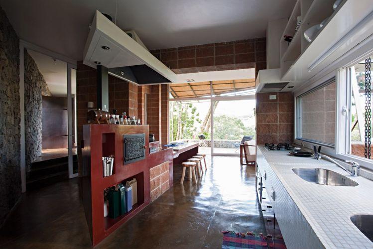 Acabada com pastilha de vidro da Jatobá, a bancada contém duas cubas e recebe luz natural proveniente da abertura estruturada com esquadria em PVC da Shine Windows. À esquerda, o corredor que liga todos os blocos da casa