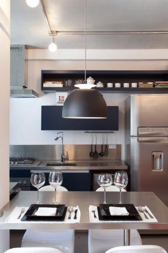 A continuidade da bancada de inox serve como mesa para refeições no apartamento de 38,75 m². Sobre ela, o pendente Bossa, criado pelo designer Fernando Prado