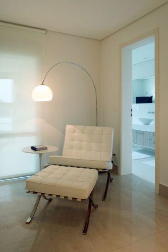 A luminária da R.R. Lustres ilumina a poltrona e pufe Brcelona, criando um canto de leitura. Na imagem ainda é possível vislumbrar o banheiro do casal, totalmente branco
