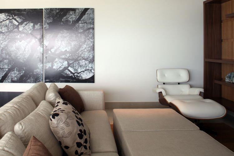 No home theater, mais um clássico do design: o conjunto de poltrona e pufe Lounge assinado por Charles e Ray Eames. Aqui, o móvel ganha estofamento branco para combinar com o sofá claro da Artefacto