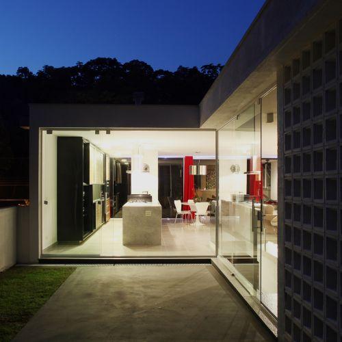 A casa, construída em um aclive, teve o volume que concentra as áreas sociais apoiado parcialmente sobre pilotis. Na extensão baseada