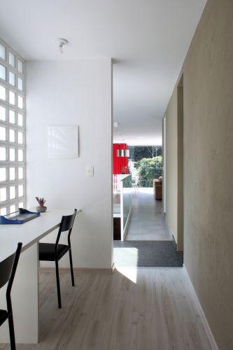 O escritório foi acomodado em uma área de passagem e tem uma bancada voltada ao pátio interno da casa. A luz entra pela parede de cobogós, escolhidos como alternativa ao painel de vidro e que oferece luz