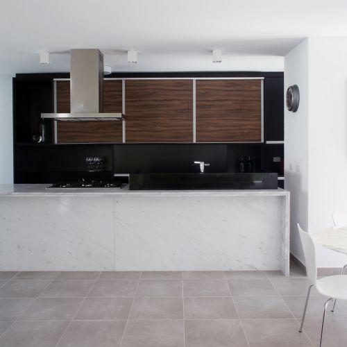 A bancada da cozinha foi executada com mármore branco espírito santo e granito preto são gabriel, opções vistosas e em conta