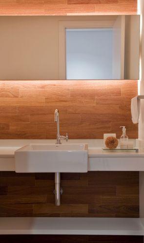 No lavabo, o projeto preservou a bancada em mármore branco piguês, louças e metais. A parede foi revestida com o mesmo tipo de taco aplicado no piso (fornecido pela Pau Pau), fazendo a ligação com a área social. A iluminação indireta vem de trás do espelho de desenho horizontal, construído pela Takae