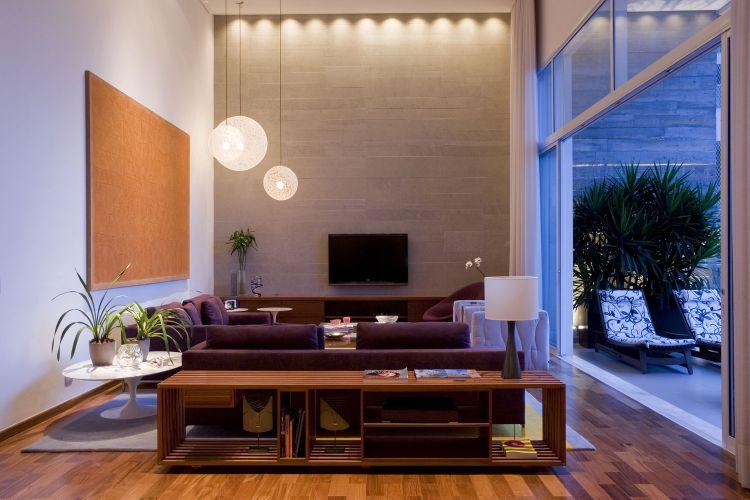 Com cortinas e portas de correr abertas, a varanda complementa o estar. Nesta foto é possível observar a semelhança da textura da parede revestida de limestone, no estar, e a marcada pelas fôrmas para concreto, no terraço