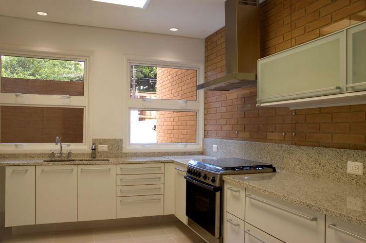 A cozinha generosa e distribuída em L ganhou tampos em granito, integrados aos armários, cubas e fogão. As janelas maxim-air (abrem para fora deixando passagem para o ar embaixo e em cima) garantem a ventilação do ambiente