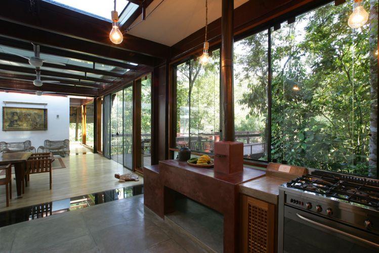 As lâmpadas da cozinha são artesanais. No piso, cimento queimado. Faixas de vidro no piso permitem ver a vegetação sob a casa