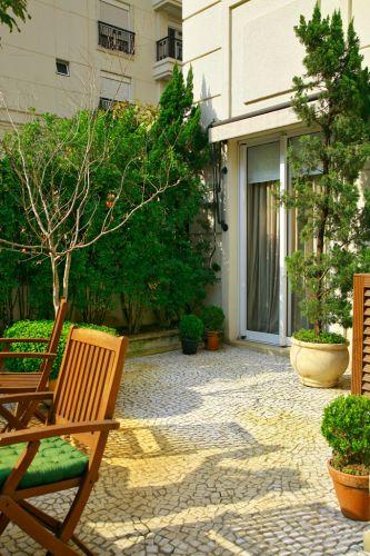 Porta de acesso de um dos quartos para o jardim. Os pinheiros nas laterais da porta são kaizuca, (Juniperus chinensis torulosa) e a árvore com galhos secos é uma jabuticabeira (Plinia trunciflora). Projeto de Gigi Botelho para o jardim de um apartamento térreo em São Paulo