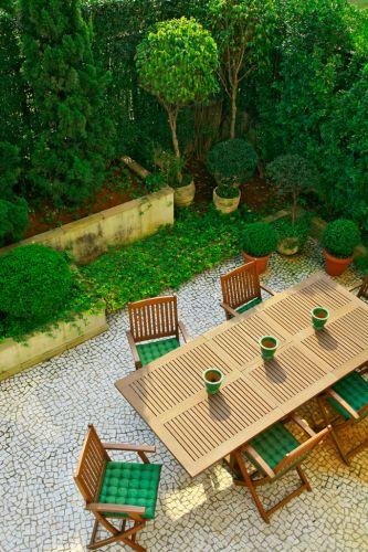 Visto do alto, o projeto de paisagismo feito por Gigi Botelho para a área externa de um apartamento térreo em São Paulo revela sua composição, protagonizada pelo SPA e pelo verde. A vegetação rente ao muro é murta (Murraya paniculata). Os pinheiros são kaizuka (Juniperus chinensis torulosa) e os arbustos esculpidos em formato redondo são buxinho (Buxus sempervirens). A forração do jardim é grama-amendoim (Arachis repens) e o piso é de mosaico português. Projeto da paisagista Gigi Botelho para a área externa de um apartamento térreo, em São Paulo