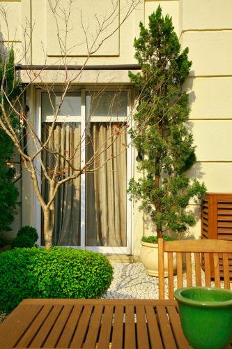 Gigi Botelho colocou vasos com pinheiros da espécie kaizuca (Juniperus chinensis torulosa) ladeando a porta do quarto que se abre para a área externa de um apartamento térreo em São Paulo. A árvore outonal, sem folhas, é uma jabuticabeira (Plinia trunciflora). O arbusto esculpido em formato ovalado é um buxinho (Buxus sempervirens)