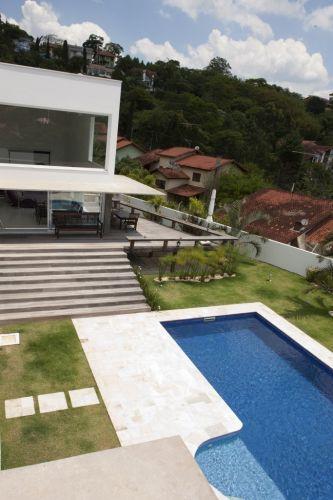 O grande deck de madeira que leva à piscina, é coberto pela aba de concreto aparente. O lance de degraus empresta certa dramaticidade à área de lazer da casa na Granja Viana, zona sul de São Paulo, projetada por Gilberto Belleza