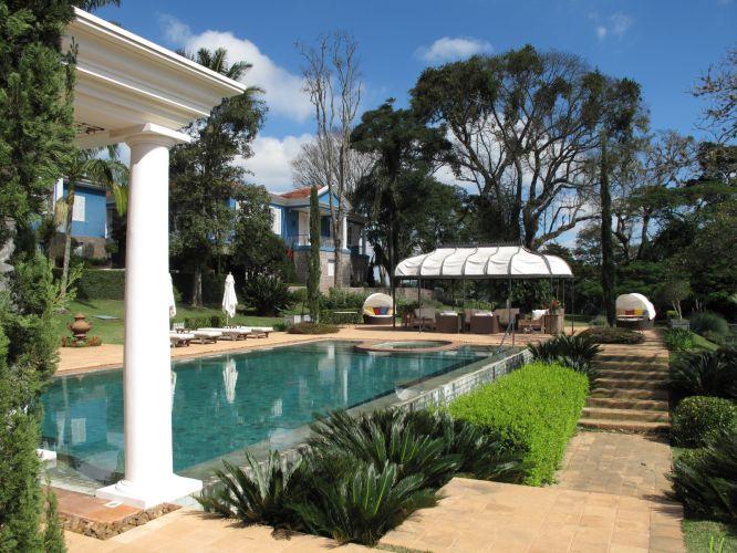 Na extremidades da piscina junto ao ambiente coberto de estar foi instalado um SPA, identificado pelo contorno ovalado de plaquetas de tijolos